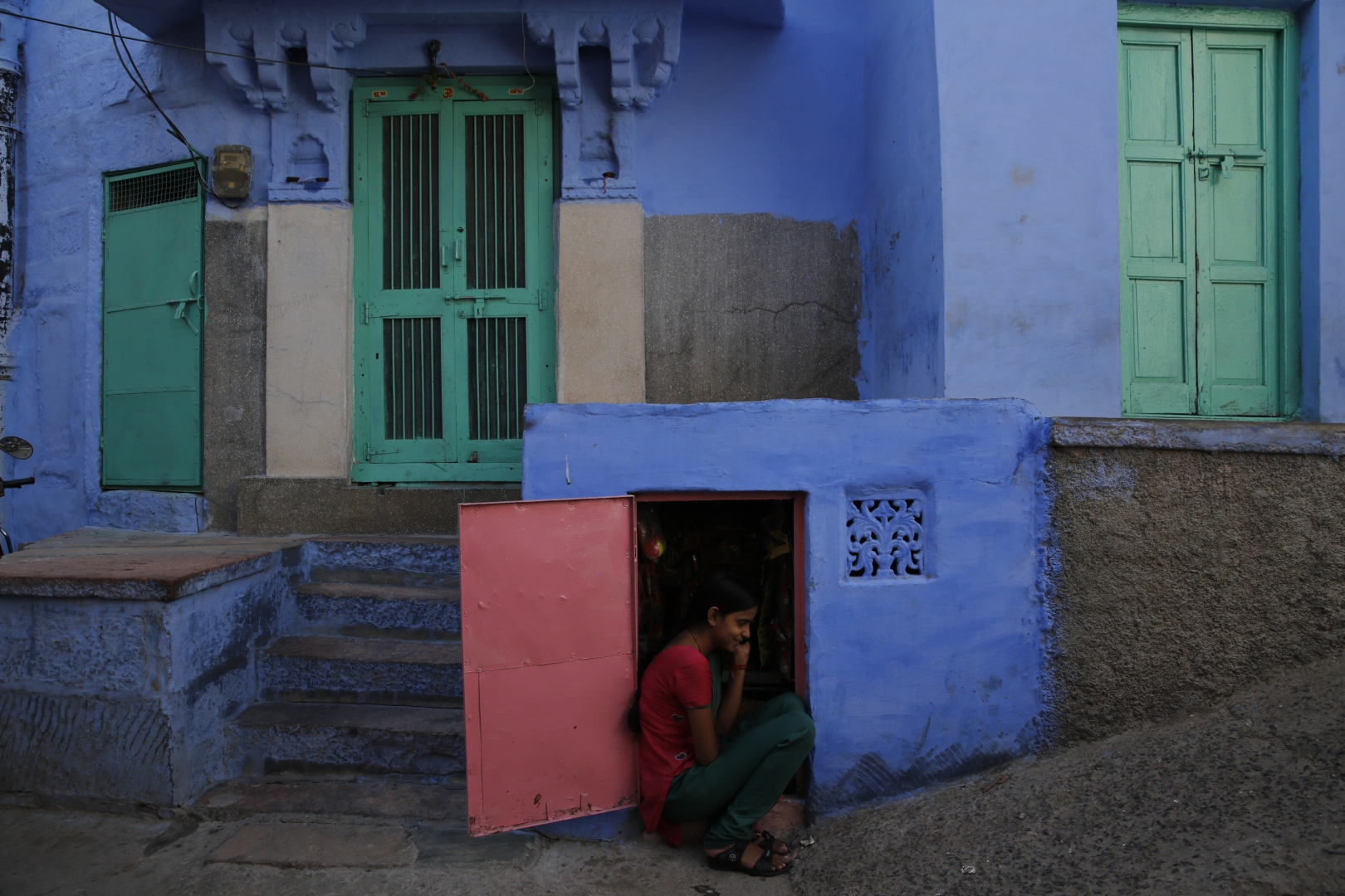 Девушка — продавщица в лавочке. Очень часто небольшие лавчонки, в которых торгуют табаком или закусками, расположены в подвальных помещениях жилых зданий