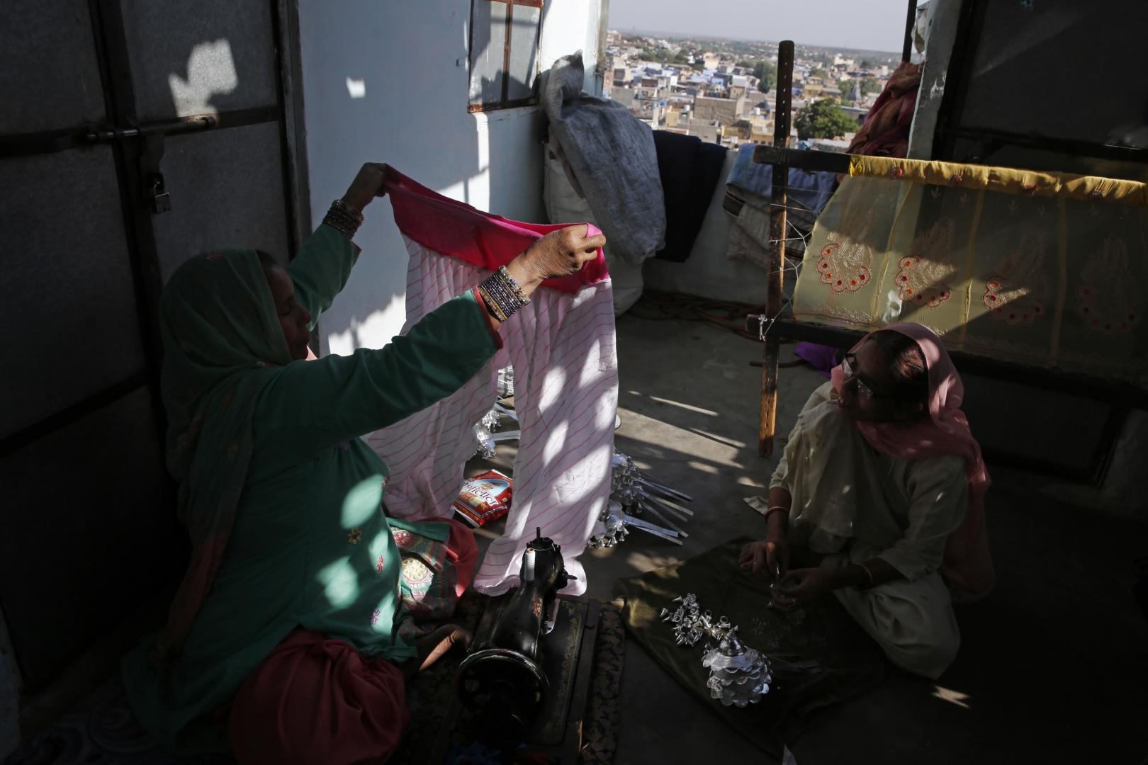 Женщины латают старые вещи на веранде дома