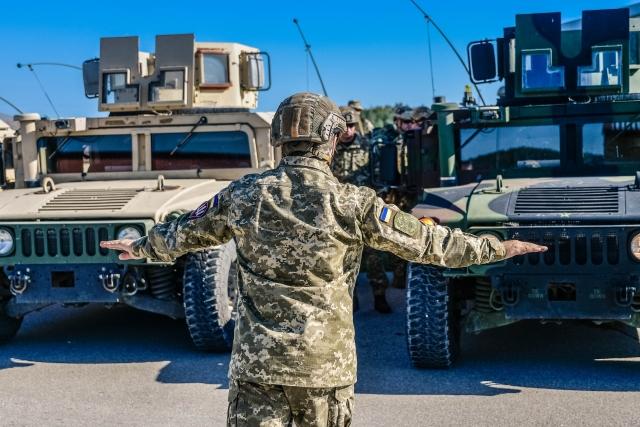 Украинский военный перед американскими автомобилями «Хаммер»