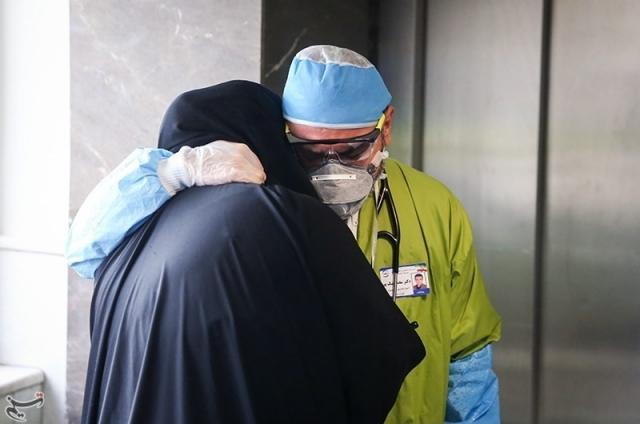 Иранский врач утешает родственников  пациента, умершего от COVID-19