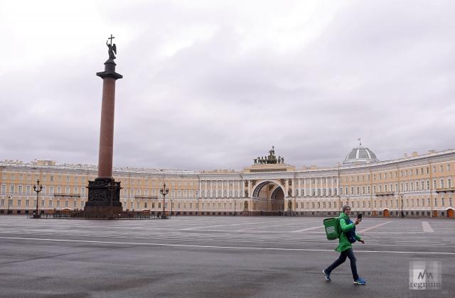 Доставщик еды идет по Дворцовой площади во время карантина