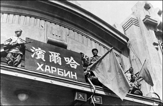 Советские бойцы водружают флаг над зданием вокзала. Харбин 1945 г