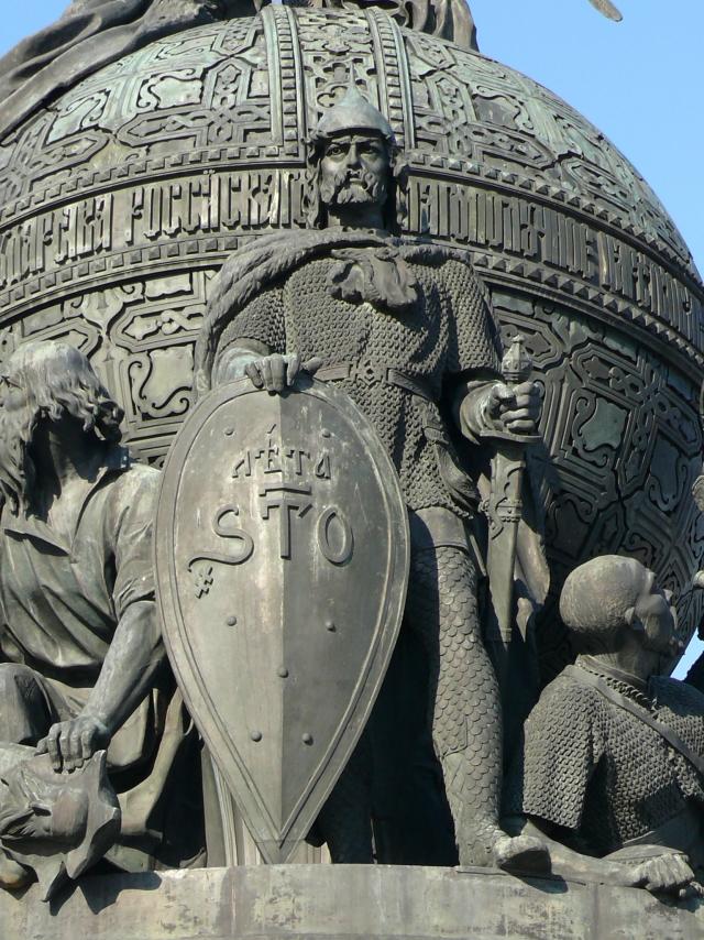 Скульптурная группа «Призвание варягов на Русь» на памятнике «Тысячелетие России» в Великом Новгороде. В центре — первый князь Рюрик в остроконечном шлеме с остроконечным щитом, в звериной шкуре, наброшенной на плечи