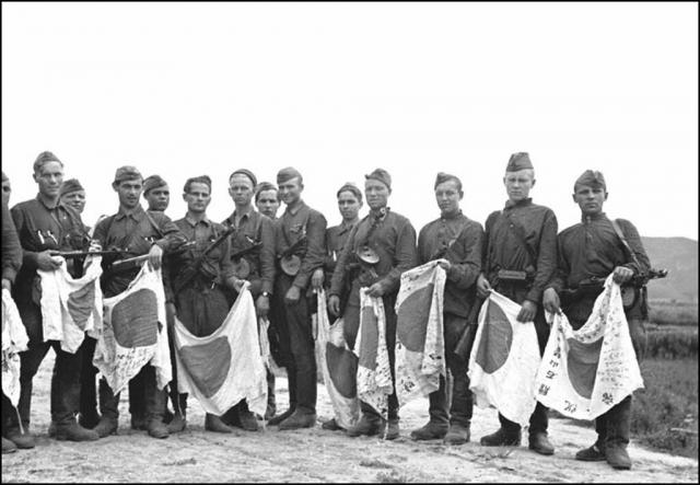 Советские солдаты с трофейными японскими флагами. Август 1945