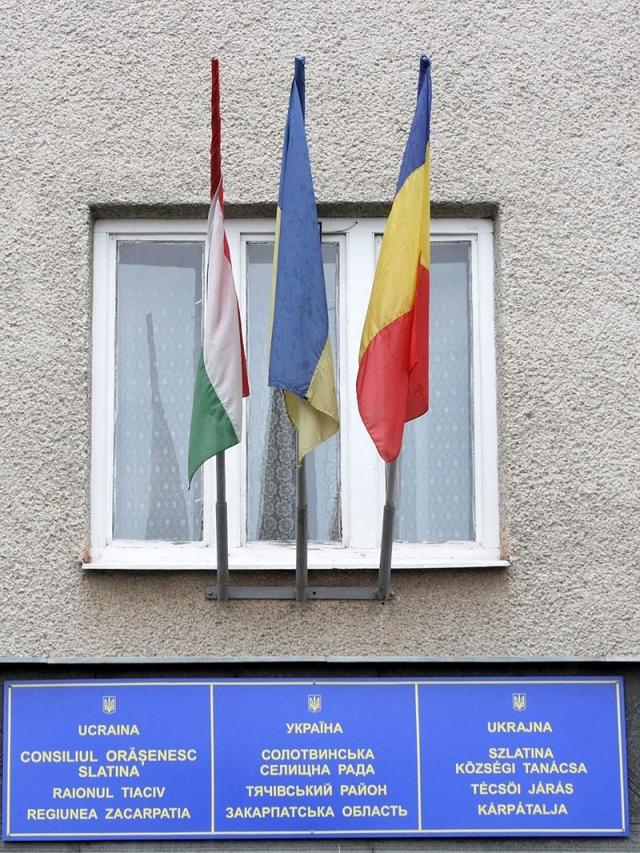 Флаги Венгрии и Румынии и надписи на венгерском и румынском языках на здании Солотвинского совета. Западная Украина