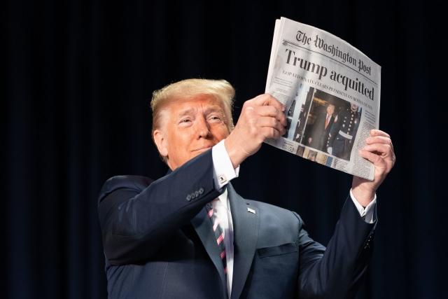 Дональд Трамп показывает газету The Washington Post с заголовком «Трамп оправдан»