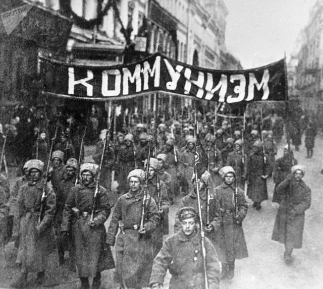 Колонна революционно настроенных солдат с лозунгом «Коммунизм» идет по Никольской улице в Москве. 1917 год