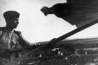 Боец РККА устанавливает красный флаг на крыше дома в одном из населенных пунктов Южного Сахалина. 1945
